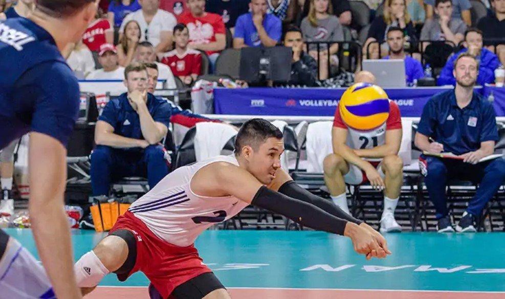 A men's volleyball player digs a ball