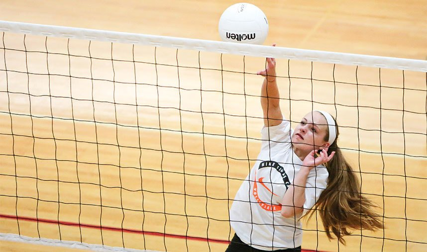 Volleyball player hits at the net