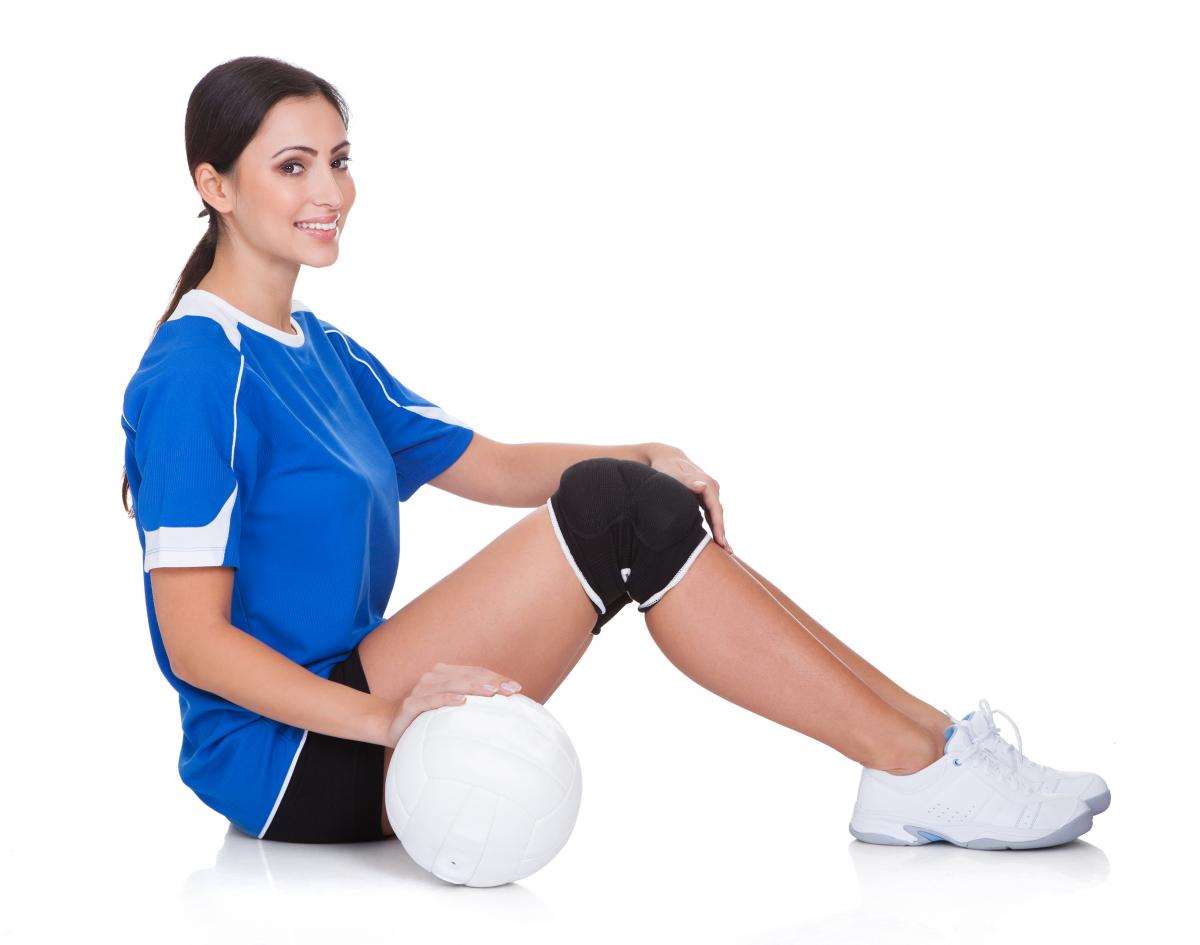 Volleyball player sits holding a volleyball