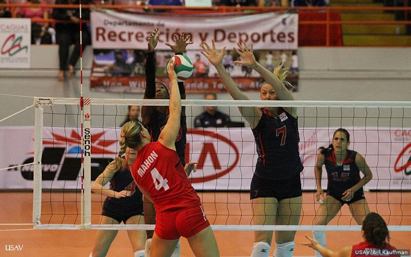 Volleyball players block an opponent's hit