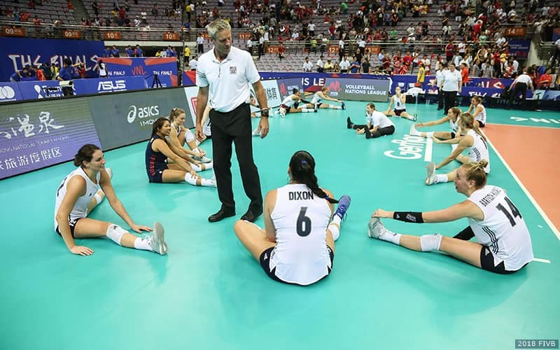 Volleyball coach talks with his players as they stretch
