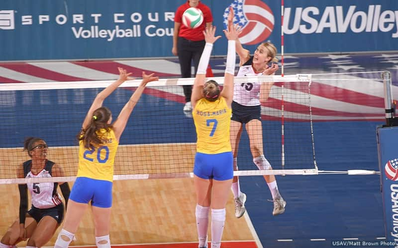 Woman hits volleyball past two opposing blockers