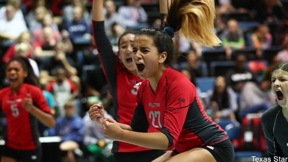Female volleyball players celebrate winning a point