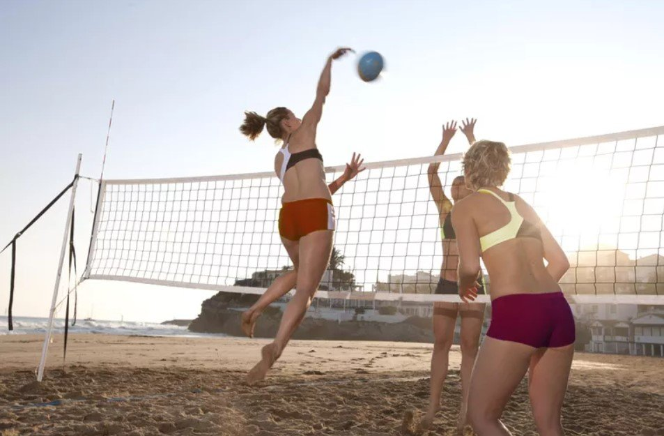 Woman leaps high to spike a volleyball at the beach